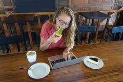 La chica joven trabaja en el ordenador y la torta, comida en el ordenador, un mún hábito come Imagen de archivo