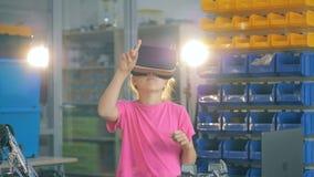La chica joven trabaja en un cuarto del laboratorio en los vidrios de Vr, colocándose cerca de la tabla 4K metrajes