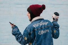 La chica joven trasera del inconformista está sosteniendo un café y está mirando el teléfono Foto de archivo libre de regalías