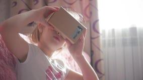 La chica joven utiliza la cartulina de la realidad virtual VR, un dispositivo con cuál puede experimentar realidad virtual en un  almacen de metraje de vídeo