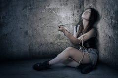 La chica joven utiliza las drogas en el cuarto de la esquina Foto de archivo libre de regalías