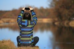 La chica joven utiliza su móvil para hacer la foto Fotos de archivo libres de regalías