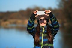 La chica joven utiliza su móvil para hacer la foto Imagen de archivo