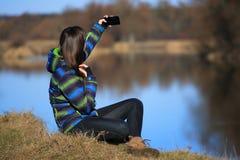 La chica joven utiliza su móvil para hacer la foto Foto de archivo libre de regalías