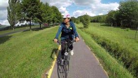 La chica joven va con la bici en un camino de la bici en Hungría almacen de video