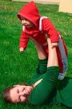 La chica joven y su niño mienten en la hierba verde Foto de archivo