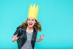 La chica marchosa en la chaqueta de cuero y el partido coronan en fondo azul en colores pastel que celebra y que baila Partido, d Foto de archivo libre de regalías