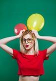La chica marchosa en vidrios de moda es que hace muecas y de mirada de la cámara que sostiene los balones de aire amarillos y roj Foto de archivo libre de regalías