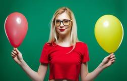 La chica marchosa en vidrios de moda es que hace muecas y de mirada de la cámara que sostiene los balones de aire amarillos y roj Fotografía de archivo libre de regalías