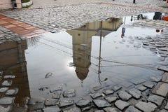 La chiesa cattolica ha riflesso in una pozza sulla strada del ciottolo Immagine Stock
