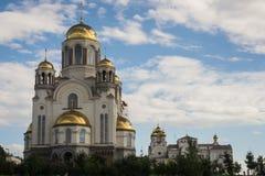 La chiesa del paese con il cimitero e la guglia alta il giorno di estati contro la nuvola blu hanno fissato il cielo Fotografie Stock