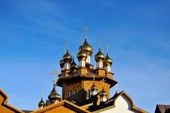 La chiesa di legno con le cupole dorate è stata consacrata dal sole contro un fondo del cielo blu La Russia, Belgorod Fotografie Stock Libere da Diritti