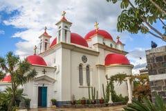 La chiesa greco ortodossa rosso-a cupola dei dodici apostoli vicino alla riva del mare della Galilea a Capernaum, Israele fotografie stock