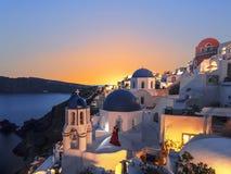 La chiesa greco ortodossa sulle acque del fondo del mar Egeo a OIA al tramonto La Grecia Immagine Stock