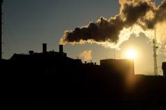 La chimenea de la central eléctrica que fumaba en la puesta del sol hecha excursionismo entonó imagen Imagenes de archivo