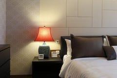 La chimenea del rojo al lado de la cama Foto de archivo