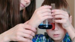La chimica sperimenta a casa Il ragazzo esamina due liquidi dei colori differenti in una provetta ed in una boccetta video d archivio