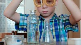 La chimica sperimenta a casa Il ragazzo versa l'acqua dalla bottiglia nella boccetta facendo uso di una pipetta stock footage