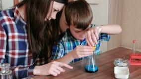 La chimica sperimenta a casa Il ragazzo versa il liquido dal tubo nella boccetta facendo uso di un imbuto video d archivio