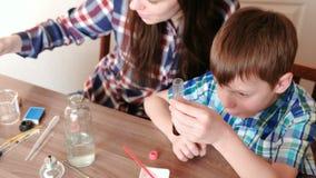 La chimica sperimenta a casa La mamma aggiunge una goccia di pittura blu alla provetta con liquido rosso stock footage