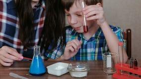 La chimica sperimenta a casa La mamma ed il figlio fanno una reazione chimica con il rilascio di gas nella boccetta archivi video