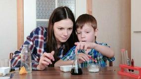 La chimica sperimenta a casa La mamma ed il figlio fanno una reazione chimica con il rilascio di gas nella boccetta stock footage