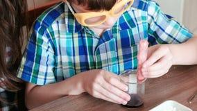 La chimica sperimenta a casa La mamma ed il figlio fanno una reazione chimica con il rilascio di gas nella provetta stock footage