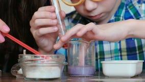 La chimie expérimente à la maison Le garçon touche le liquide dans le becher avec son doigt banque de vidéos