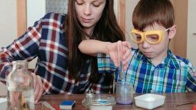 La chimie expérimente à la maison Liquide de versement de garçon d'un tube à essai dans le becher, mélange de maman il a utilisé  banque de vidéos