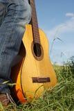 La chitarra che riposa sulla a equipaggia il piede Immagine Stock