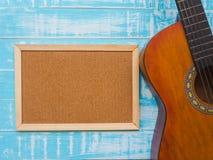 La chitarra ed il bordo sul fondo di legno blu di struttura Musica da fotografia stock libera da diritti