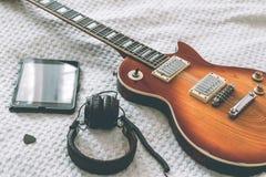 La chitarra elettrica è su una coperta bianca Fotografia Stock