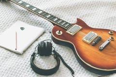 La chitarra elettrica è su una coperta bianca Fotografie Stock