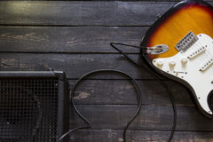 La chitarra elettrica con l'amplificatore si è collegata da cavo sulla parte posteriore di legno Fotografia Stock Libera da Diritti