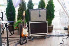 La chitarra, l'altoparlante ed il microfono elettronici stanno nel ristorante fotografia stock