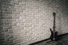 La chitarra sta vicino alla parete di pietra fotografia stock