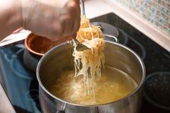 La choucroute de transfert de cuisinier du pot dans la casserole photographie stock libre de droits