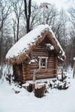 La choza se coloca en el bosque en nieve del invierno Imágenes de archivo libres de regalías