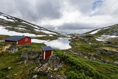 La choza y el toilette de madera rojos están en la frontera del lago Galgebergstjornane en Noruega fotografía de archivo