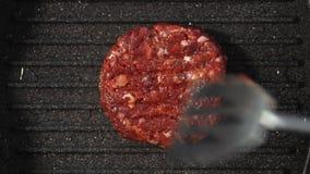 La chuleta de la carne picadita, asperjada con las especias picantes se coloca en la parrilla en aceite Visi?n superior almacen de video