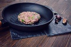 La chuleta de la carne picadita con las hierbas y el ajo en un arrabio asan a la parrilla la cacerola Imagenes de archivo