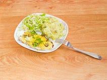 La chuleta de cerdo cocida con adorna de purés de patata y de ensalada Foto de archivo