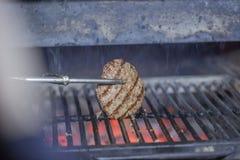 La chuleta y el queso de la hamburguesa se cocina en josper en medio del carbón ardiente para una celebración de días festivos imagen de archivo