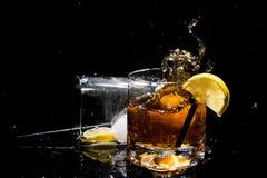 La chute de la glace dans le verre de qualité de whiskey fait un grand nombre éclabousse et l'autre verre se trouve du côté avec  Photos libres de droits