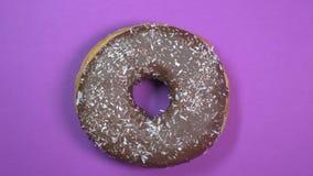La ciambella luminosa e variopinta del cioccolato con la noce di cocco scheggia, macro colpo, filante su un fondo porpora video d archivio