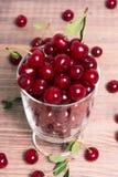 La ciliegia fresca fruttifica in una ciotola di vetro su una tavola di legno Fotografia Stock