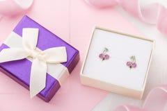 La ciliegia ha modellato gli orecchini con i cristalli in contenitore di regalo sul rosa avvolge Fotografia Stock