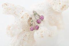 La ciliegia ha modellato gli orecchini con i cristalli rosa su fondo bianco Fotografia Stock Libera da Diritti