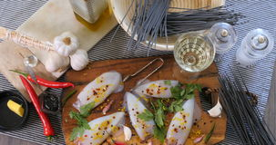 La cima del carrello giù zuma in considerazione degli ingredienti per pasta con i calamari seppia ed inchiostro stock footage