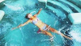 La cima del punto di vista della giovane donna graziosa di abbronzatura in bikini ed occhiali da sole nuota nella piscina in acqu archivi video
